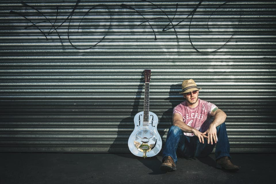 Lawless Luke, Delta Blues Slide Guitar player & composer, grey shutter graffiti background sat down