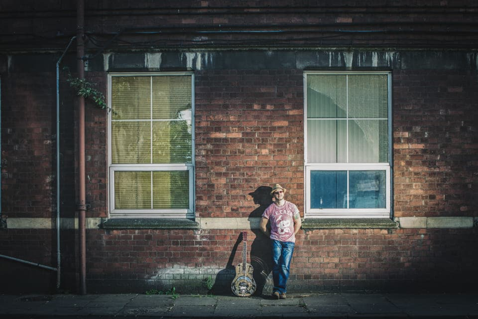 Lawless Luke, Delta Blues Slide Guitar player & composer, Delta Blues Bottleneck Slide Guitar Youtube Video creator, leaning against red brick building with light flare
