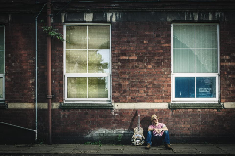 Lawless Luke, Delta Blues Slide Guitar player & composer, sat down against red brick building