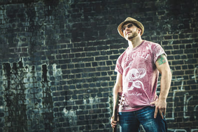 Lawless Luke, Delta Blues Slide Guitar player & composer, holding resonator guitar with grime wall backdrop