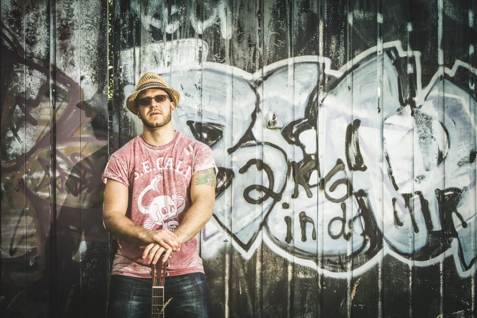 Lawless Luke, Delta Blues Slide Guitar player & composer, graffiti background and resonator guitar