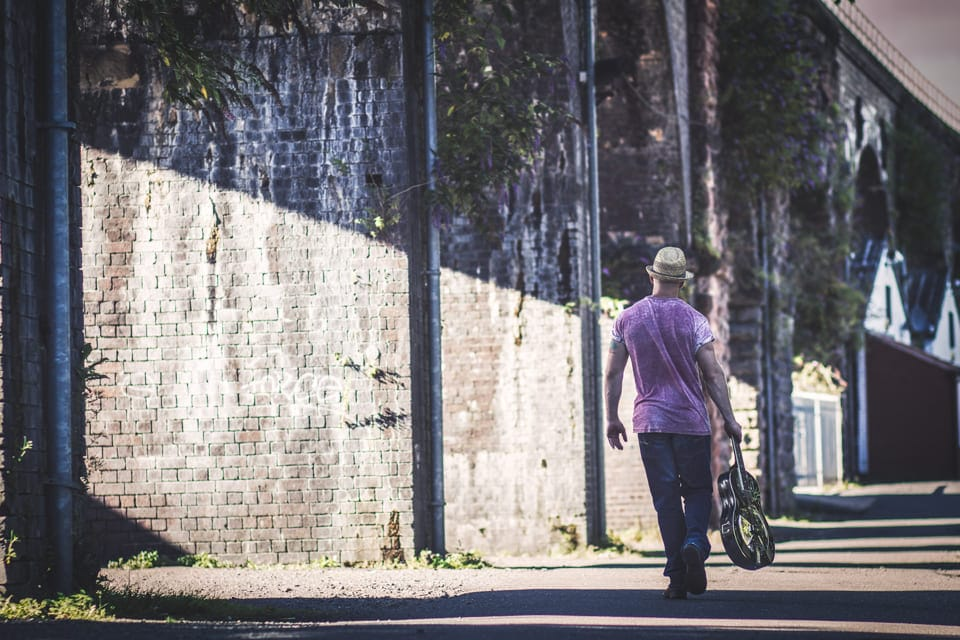 Lawless Luke, Delta Blues Slide Guitar player & composer, walking away near bridge with resonator guitar