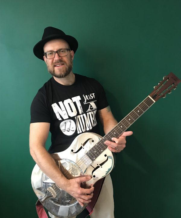 Lawless Luke wearing this 'Not Just A Number' limited edition t-shirt with resonator guitar