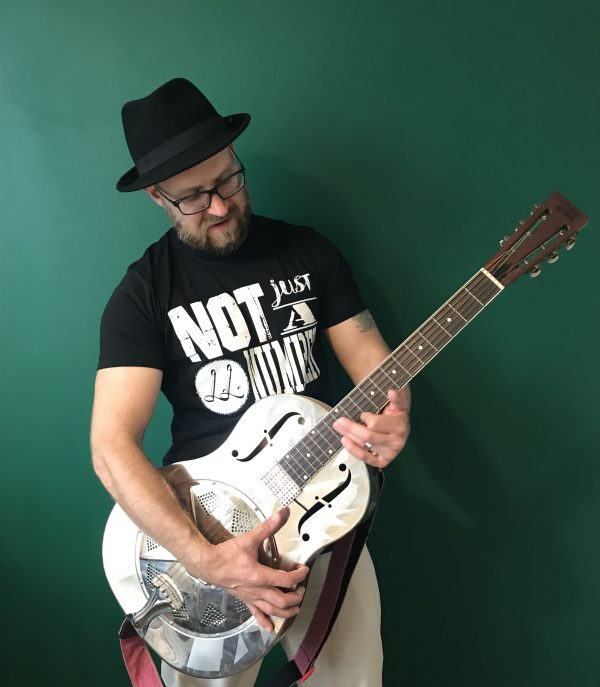 Lawless Luke wearing this 'Not Just A Number' limited edition t-shirt with resonator guitar V1